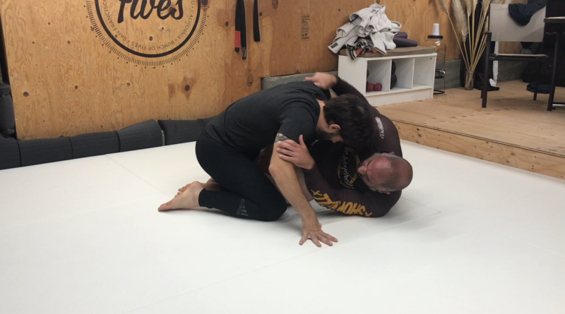 Two grapplers training in a home gym.