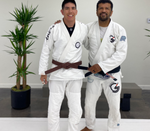 Michael 'Reige' Tatum (left) getting promoted to brown belt by Giva Santana (right)